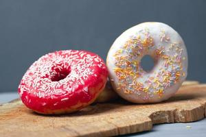 Two assorted glazed donuts on a wooden plank and gray background photo