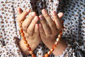 manos de mujer rezando con cuentas foto