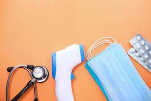 Mascarillas quirúrgicas, termómetro y desinfectante de manos sobre fondo naranja foto
