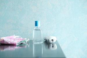 mascarillas quirúrgicas, termómetro y desinfectante de manos en la mesa foto