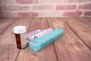 Cerca del contenedor, pastillero y blister en la mesa foto