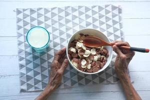 Top view of senior women eating chocolate corn flakes in a bowl photo