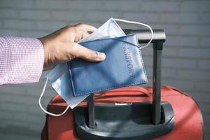 sosteniendo el pasaporte en la mano con la maleta foto
