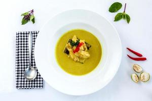 Green Thai curry on a white dish and white background photo