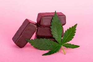 Chocolate candy with medical cannabis on pink background photo
