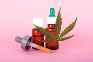 Natural cannabis medicine, marijuana oil extract on pink background photo