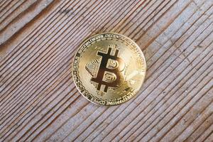 Close up of a Bitcoin cryptocurrency coin on a wooden background