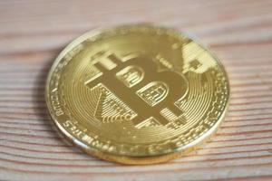 Bitcoin on a wooden surface background. Bitcoin cryptocurrency. Golden metal bitcoin crypto currency concept photo