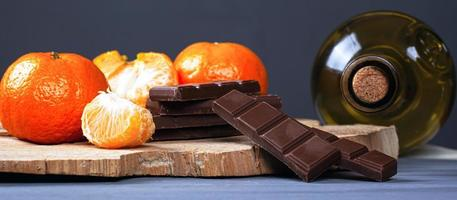 Bottle of white wine with slices of milk chocolate and tangerines on a wooden stand photo