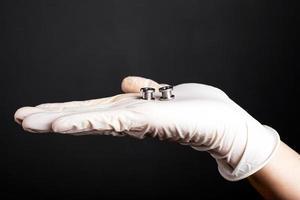 Mano en un guante blanco desechable sostiene túneles perforantes sobre un fondo oscuro foto