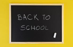 Hand-drawn title welcomes Back to School on black chalkboard among yellow vivid background.