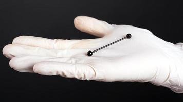 Mano en un guante blanco sostiene joyería de oreja perforadora de cartílago foto
