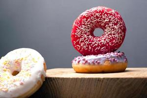 Holiday donuts with violet and red glaze on a gray background