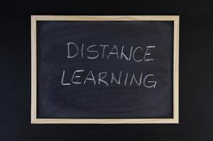 Hand-drawn title Distance Learning on a black chalkboard with wooden frame.