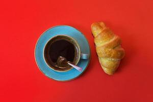 Coffee cup and fresh croissant isolated on red background with copy space. Top view on fresh breakfast with coffee and baked sweet pastries. photo