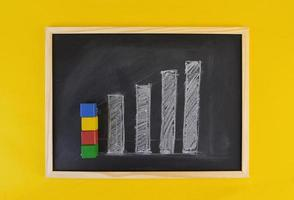 Hand-drawn progress growing chart on black chalkboard among yellow vivid background. Business concept picture frame.
