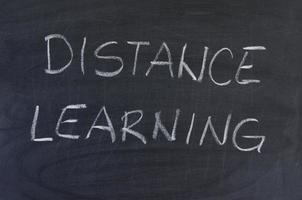Hand-drawn title Distance Learning on black chalkboard.