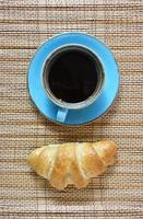 Coffee cup and fresh croissant isolated on vintage textured brown background. Top view on fresh breakfast with coffee and baked sweet pastries. photo