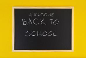 Hand-drawn title Welcome Back to School on black chalkboard among yellow vivid background.