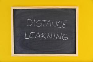Hand-drawn title Distance Learning on black chalkboard among yellow vivid background.