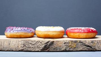 Three assorted glazed donuts of different colors on a wooden plank on a gray background