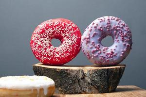 Two colored donuts on wood stump close-up photo