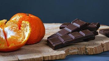Chocolate y mandarinas sobre tablero de madera y fondo oscuro foto
