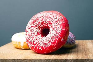 Deliciously tasty red donut with white powder on a wooden stand on a gray background photo