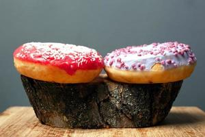 Colorful donuts on wood stump photo