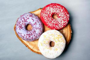 Flat lay of assorted donuts with frost on gray background photo