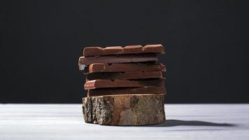 Pieces of milk chocolate on a wooden stand on a gray background