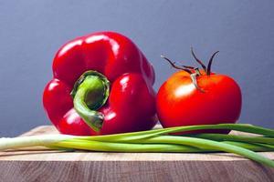 Verduras en un estante de madera sobre un fondo gris foto