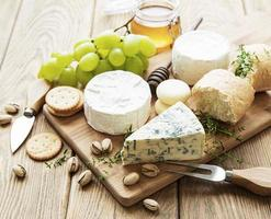 Cheese selection, honey, and grape on an old wooden background
