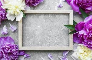 Marco de madera rodeado de hermosas peonías rosas sobre un fondo de hormigón gris foto