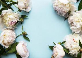 flores de peonía sobre un fondo azul pastel foto