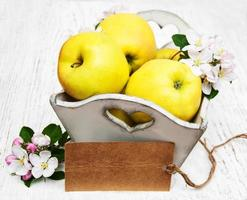 Box with apples and apple tree blossoms and an empty tag on a wooden table
