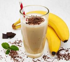Batido de plátano con chocolate sobre un fondo de madera blanca antigua foto