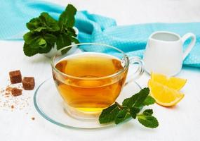 Cup of tea with lemon and mint photo
