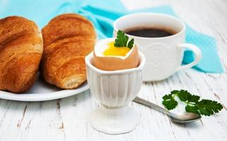 Croissant, boiled egg, and coffee on an old wooden table photo