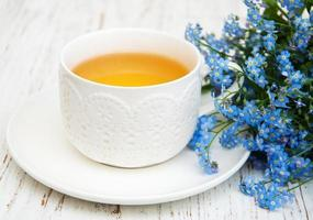 Cup of tea and forget me not flowers on a wooden background