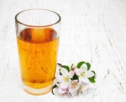 Vaso de jugo de manzana con flores sobre un fondo de madera foto