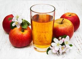 Vaso de jugo de manzana con manzanas y flores sobre un fondo de madera foto
