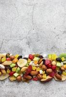 Various dried fruits and nuts on a gray concrete background