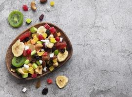 Bowl with various dried fruits and nuts on a gray concrete background