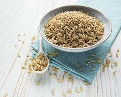 Raw brown rice on a white wooden background photo