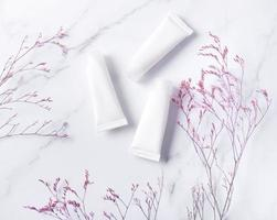 White tubes of cream on a marble background