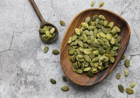Wooden plate with pumpkin seeds photo