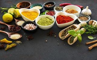 Various spices in a bowl on black concrete background. Top view copy space. photo