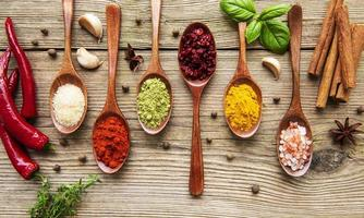 Various colorful herbs and spices on wooden table photo