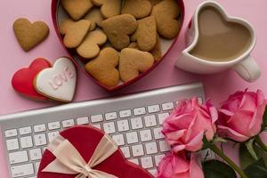 Valentine's Day cookies, flowers, and coffee on pink background